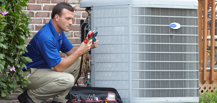 Technician repairing a Carrier air conditioner