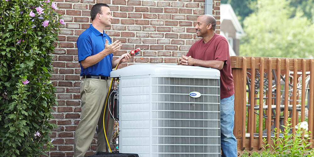 HVAC technician shows homeowner how his new air conditioner works on a nice day.