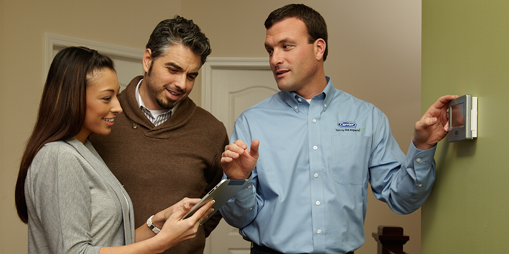 Tech shows woman and man homeowners how to work their new air purification system.