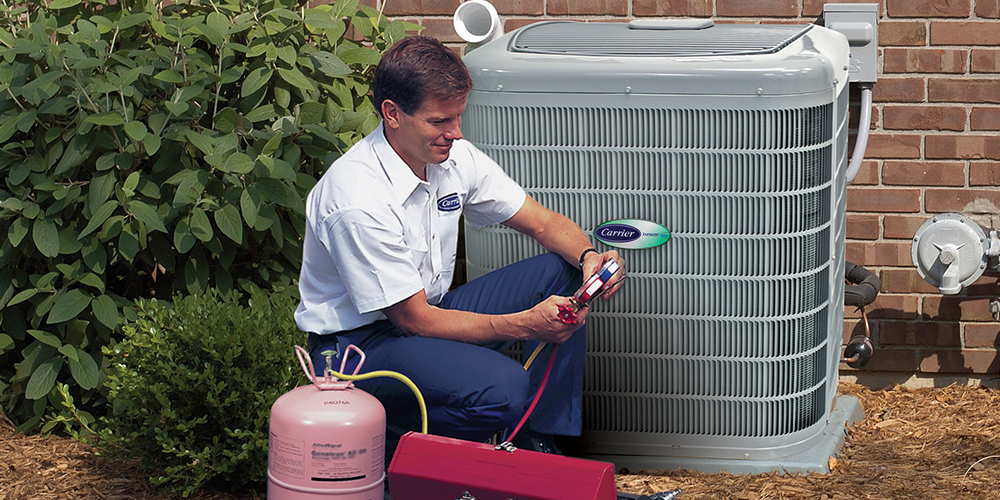 Technician in white shirt examines an air conditioner blowing warm air outside a customer's house.
