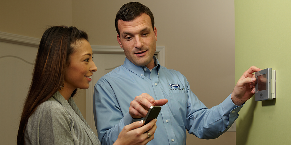 Technician shows young female homeowner how to use her new Wi-Fi thermostat.